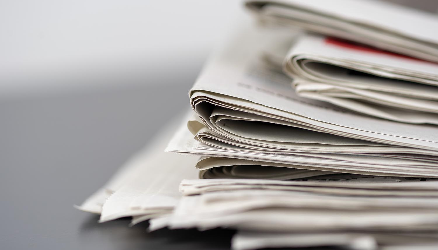 Closeup shot of several newspapers stacked on top of each other